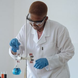smiling-scientist-examining-chemical-liquid-in-modern-lab-3825414